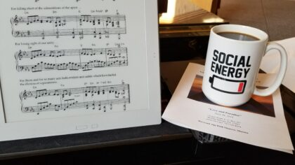 """Social Energy"" coffee mug next to the sheet music for ""We Begin Again in Love"""